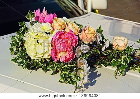 Decorative flowers bouquet on white wedding car taken closeup.