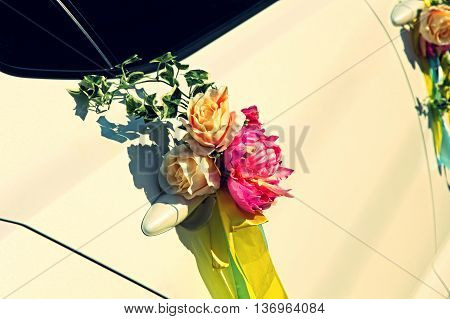 Wedding flowers bouquet on car door taken closeup.Toned image.
