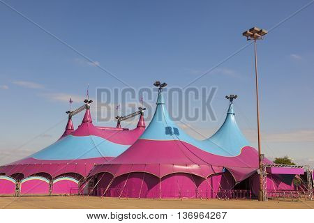 Colorful circus big top tent against a blue sky