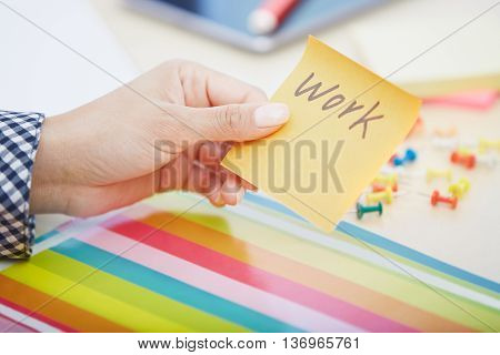 Human hand holding adhesive note with Work text
