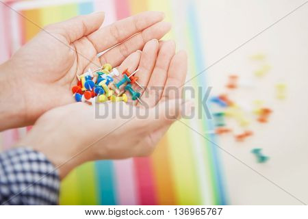 Close-up photo of the woman hands with colorful pushpins