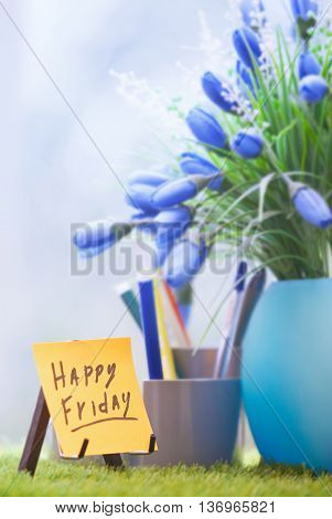 Adhesive note with Happy Friday text at green office