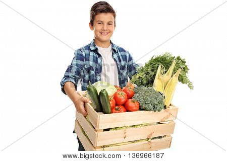Joyful child carrying a wooden crate full of fresh vegetables isolated on white background