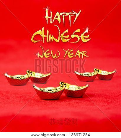 Happy Chinese new year word with golden texture with golden ingots on red felt fabricChinese Language mean