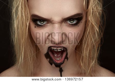 Scary screaming Girl with black Paint Drips on her Mouth