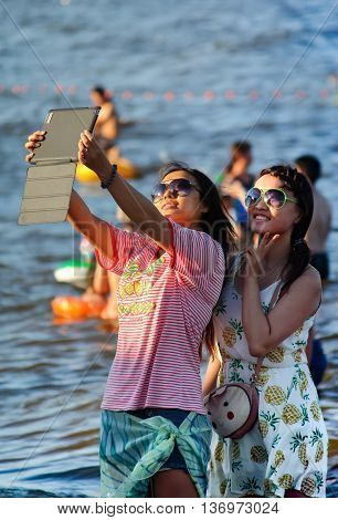 Beidaihe China. August 9 2012. Two young girls in sunglasses doing selfie on the computer tablet