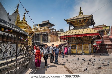 KATHMANDU NEPAL - APRIL 7 2016 : People walk around Stupa in Swayambhunath (monkey temple), one of famous landmarks in Kathmandu valley Nepal.