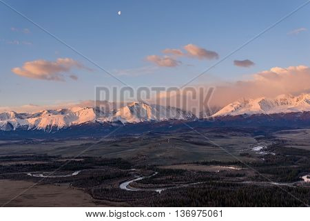 Scenic spring landscape with mountains covered with snow valley winding river and clouds in the pink light of the sun at sunrise