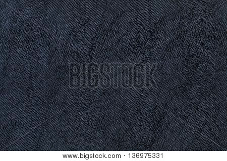 Dark purple wavy background from a textile material. Fabric with natural texture closeup. Upholstery fabric pleated.