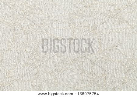 White cream wavy background from a textile material. Fabric with natural texture clousup. Upholstery fabric pleated.