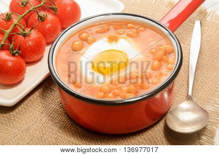 baked beans with fried egg in a red and white enamel pot