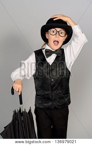 Elegant boy in a suit, bowler hat and glasses posing at studio with his umbrella. Children fashion.