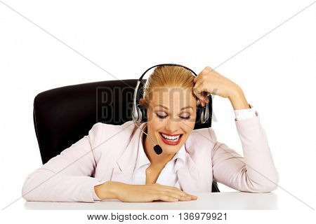 Smile helpline operator sitting behind the desk and talking through a headphones