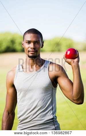 Portrait of male athlete holding short put ball in a stadium