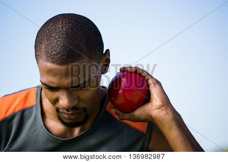 Close-up of male athlete holding shot put ball in stadium