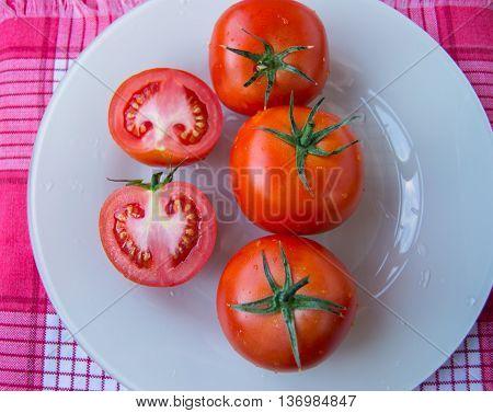 Fresh ripe tomatoes on white dish - top view.