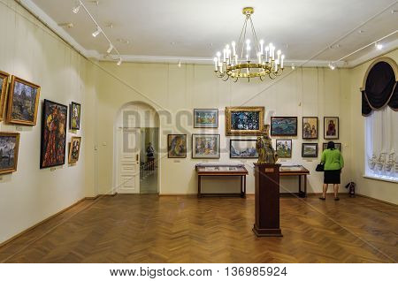 VELIKY NOVGOROD RUSSIA-JULY 1 2016. Unidentified museum visitors look pictures hanging on the walls in the showrooms of Art Museum of Veliky Novgorod