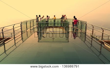 Nong Khai province Thailand- April 28 2016: Tourists walking and taking photograph on transparent sky walk to see view of Mekong River during sunset at Wat Pha Tak Suea Sangkhom district Nong Khai province Thailand.