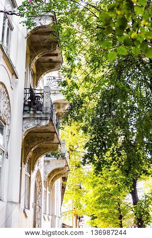 Traditional balcon of archiepiscopal palace to the strees with trees