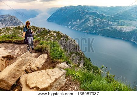 FORSAND, NORWAY - JULY 12, 2015: Girl hiker with trekking pole and looking on Lysefjorden, Norway. Lysefjorden is one of the most famous fjords in Norway.