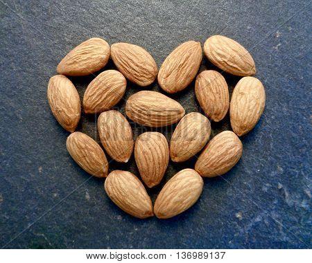 Almonds in heart shape on slate board