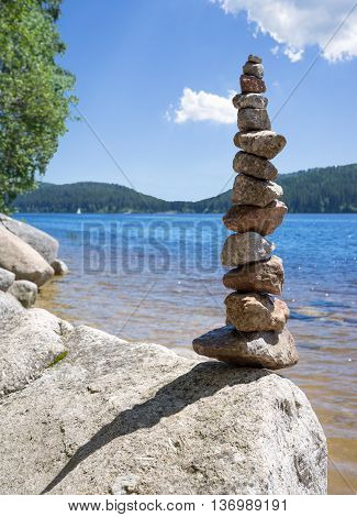 Rock balancing at a lake - artistic balanced stacking on the shore of the Schluchsee in the Black Forest, Germany.