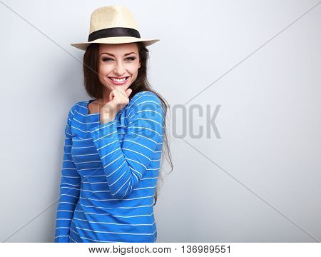 Beautiful Long Hair Laughing Woman In Blue Top And Straw Hat Looking Happy With Hand Under Face