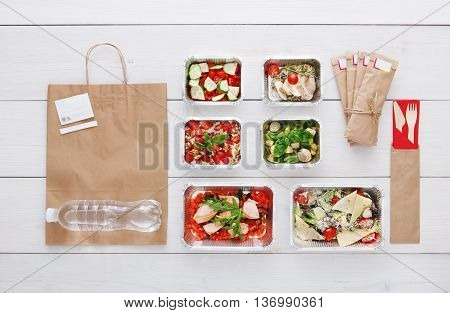 Healthy food delivery. Take away of natural organic low carb diet. Eat right concept, fitness nutrition in foil boxes, water bottle, cutlery and brown paper package. Top view, flat lay at white wood