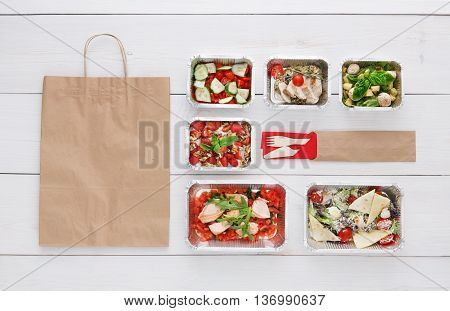 Healthy food delivery. Take away of natural organic low carb diet. Fitness nutrition in foil boxes, cutlery and brown paper package with copy space. Top view, flat lay at white wood