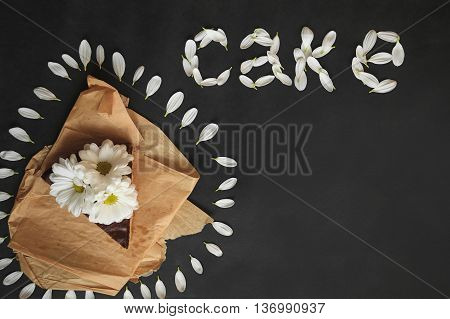Piece Of Chocolate Cake With Flowers On Craft Paper. Inscription Of The Petals
