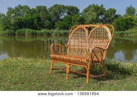 Wicker wide chair on a lakeside at summer season