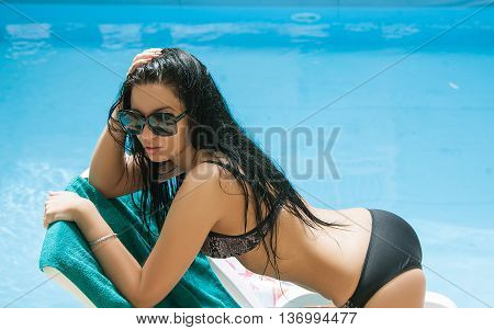Sexy woman in the dark swimsuit on the sun-tanned slim and shapely body is resting and taking sun bathes near the swimming pool