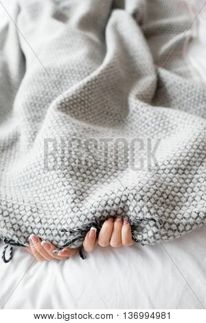 Woman hiding from the problems under the gray blanket. Photo of bed with gray blanket and two female hands, free space for text. Fear, introvert, loneliness background