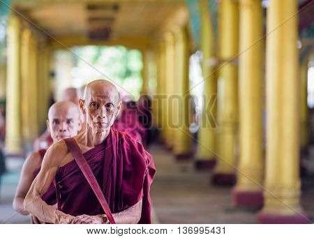 BAGO, MYANMAR - OCTOBER 19, 2015: Monks line up to receive lunchtime food offerings at Kyaly Khat Wai Monastery.