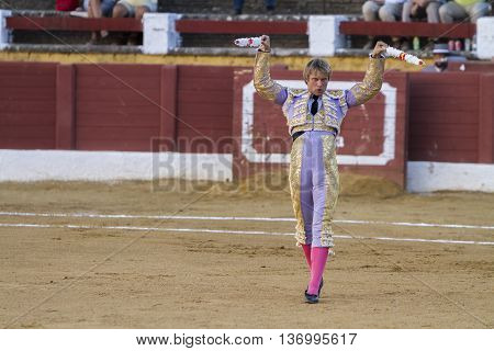 Andujar Spain - September 10 2010: The Spanish Bullfighter Ivan Garcia with flags in each hand classic of the taurine art movement in the Bullring of Andujar Spain