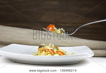 Couscous in a white ceramic plate with wooden background
