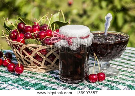 Cherry jam jar on background of basket of cherries and cherry jam