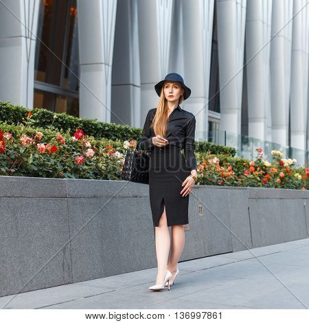 Beautiful Elegant Woman In A Stylish Hat In Business Style Clothes On A Background Of A Modern Build