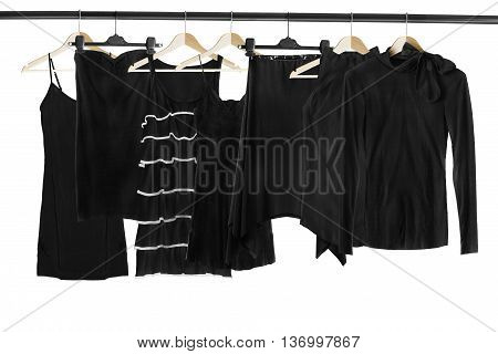 Set of black clothes on wooden clothes racks isolated over white