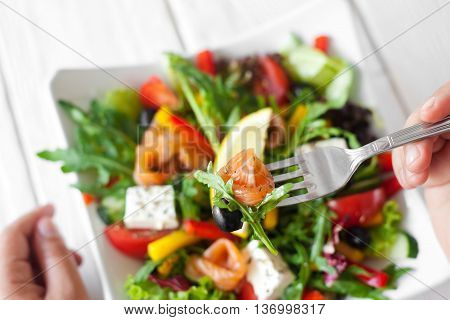 Salmon salad eating at restaurant top view. Customer hand holding fork with smoked salmon and olive, other hand near plate with salad on white wooden table. Eater pov