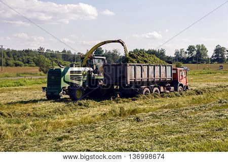 Pushkin, Russia - 2 July : on a green field in the summer of truck driving next to the combine which mows fresh grass in celebration of World UFO Day on 2 July, 2016.