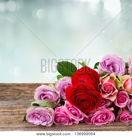 bouquet of roses and ranunculus on wood border with copy space on blue bokeh background