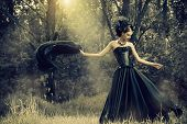 Magnificent brunette woman wearing long black dress walking in a mystic forest. The old times, the G poster