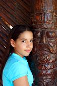 stock photo of indian totem pole  - Latin mexican teen girl smile with indian wood totem - JPG