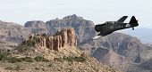 foto of superstition mountains  - An old fashion military prop plane flying low over the superstition mountains near Phoenix Arizona - JPG