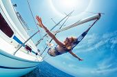 Young lady relaxing in the hammock set on the sail boat while sailing in the open sea poster