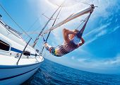 Man relaxing in the hammock set on the sail boat while sailing in the open sea poster
