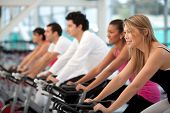 Group Of People Cycling At The Gym And Smiling