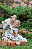 foto of mother child  - Young Mother and child Gardening - JPG