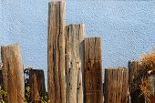 Weathered Wood Pylons In Front Of A Blue Stucco Wall poster